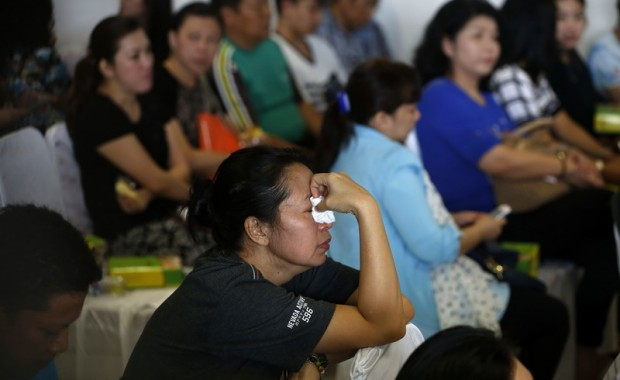 Family members of passengers onboard missing AirAsia flight QZ8501 react as they await news in Juanda International Airport, Surabaya